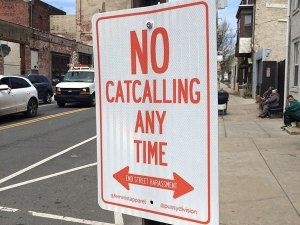 "[Image: red and white street sign that says ""No catcalling any time""]"