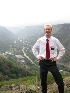 Isaac stands with his hands on his hips on a hill with a river valley behind him. He is wearing a white button down shirt with red tie, black pants, and an LDS missionary name tag.